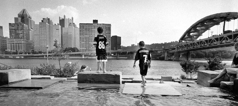 Before a preseason game, children try to cool off in a fountain along Riverside Park. Pittsburgh 2005.