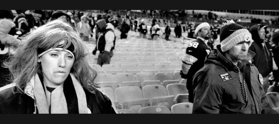 After the Patriots defeat the Steelers in the 2004 AFC Championship game, one woman cries as she waits to cheer the Steelers one last time before they leave the field. Heinz Field 2005.